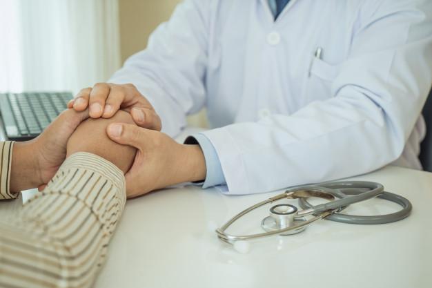 friendly-man-doctor-hands-holding-patient-hand-sitting-desk-encouragement_73503-842