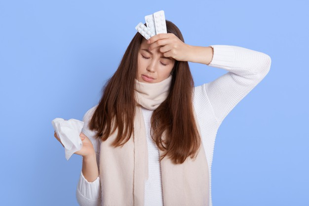upset-depressed-sick-woman-warm-scarf-casual-jumper-holding-napkin-pills-frowning-with-displeased-miserable-expression-isolated-blue-wall-keeps-eyes-closed_176532-13914